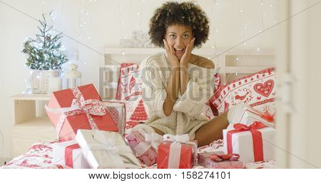 Excited young woman with a bed full of Xmas gifts