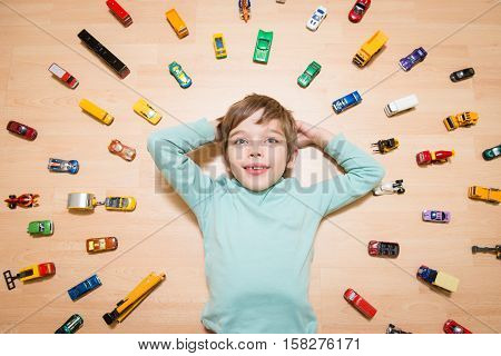 Adorable boy lying on the ground with toy cars around