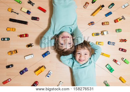Adorable brothers lying on the ground with toy cars around