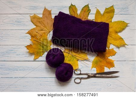 Violet yarn knit fabric wooden knitting needles scissors and yellow fallen leaves are on white vintage wooden desk. Top view.