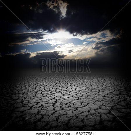 Drought cracks and dark sky clouds desert