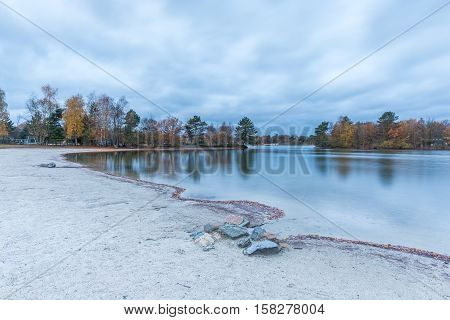 Autumn leaves accumulate at the water edge while colorful trees outline the lakeside in a forest at Kempervennen, North Brabant, Netherlands