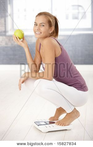 Portrait of happy squatter girl on scale holding green apple, laughing at camera.?