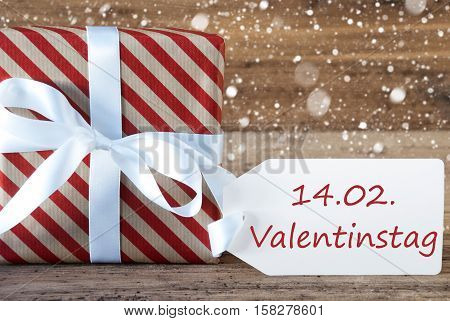 German Text Valentinstag Means Valentines Day. Christmas Gift Or Present On Wooden Background With Snowflakes. Card For Seasons Greetings. White Ribbon With Bow.