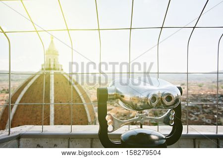 Binoculars overlooking Florence cityscape top of the cupola Duomo Santa Maria Del Fiore Florence Tuscany Italy. Useful file for your brochure flyer and site about Italy and Florence