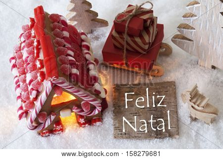 Label With Portuguese Text Feliz Natal Means Merry Christmas. Gingerbread House On Snow With Christmas Decoration Like Trees And Moose. Sleigh With Christmas Gifts Or Presents.