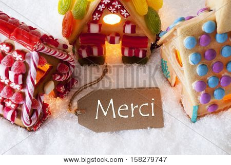 Label With French Text Merci Means Thank You. Colorful Gingerbread House On Snow. Christmas Card For Seasons Greetings