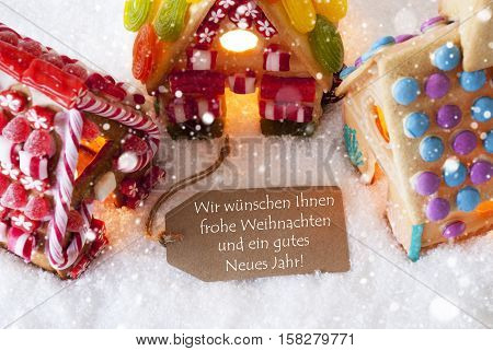 Label With German Text Wir Wuenschen Frohe Weihnachten Und Ein Gutes Neues Jahr Means Merry Christmas And Happy New Year. Colorful Gingerbread House On Snow And Snowflakes.