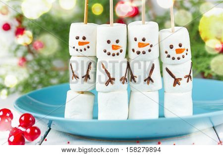 Cute snowman marshmallow pops food art idea for kids New Year and Christmas background