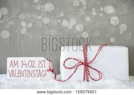 One Christmas Gift Or Present On Snow. Cement Wall As Background With Bokeh. Modern And Urban Style. Card For Birthday Or Seasons Greetings. Label With German Text Valentinstag Means Valentines Day