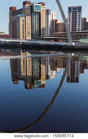 Newcastle England - October 25 2016: Gateshead Millennium Bridge reflection in River Tyne with the Baltic Centre for Contemporary Art in the background. The bridge spans the River Tyne in north east England.