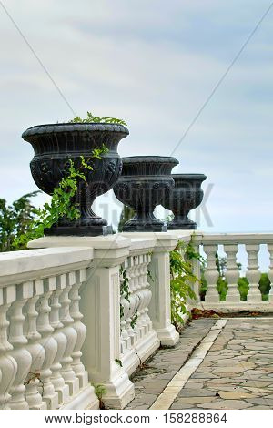 Summer terrace with white railings. On the fence are big black decorative vases. Through the railing makes its way green branches plants. Against the background of the blue sky. Sunny day. Terrace holiday house. Balcony with a stone floor. Palace terrace