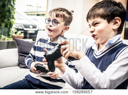 Happy children playing videogames in the living room