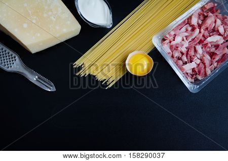 Ingredients for Pasta Carbonara on dark background with place for text. Set of products for pasta Carbonara - spaghetti bacon cream Parmesan cheese egg. Italian food concept. Copy space. Top view.