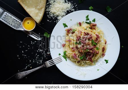 Pasta Carbonara. Spaghetti with bacon parsel and parmesan cheese. Pasta Carbonara on white plate with parmesan on dark background. Italian food concept. Top view.