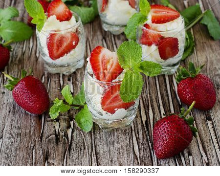 Strawberries with cream or tiramisu in small glasses with mint, vintage wooden background, selective focus