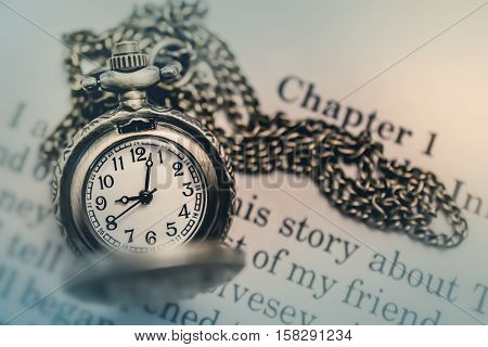 Pocket Watch on the open Book in Vintage Tone