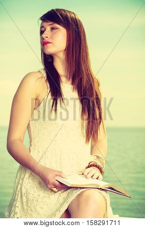 Books bookworm travel leisure time concept. Beautiful woman wearing white dress sitting on wooden hurdle near sea and reading book