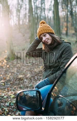 Woman posing on car in forest