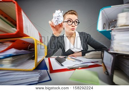 Boredom and fatigue concept. Young emotional expressive woman in office. Bored tired businesswoman with paper ball at work.