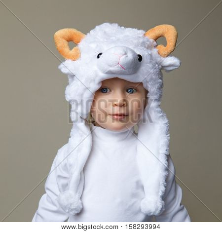 Cute adorable pretty Caucasian baby toddler with large blue eyes wearing a sheep hat hood with yellow horns on top and white shirt standing on a light background New Year concept studio