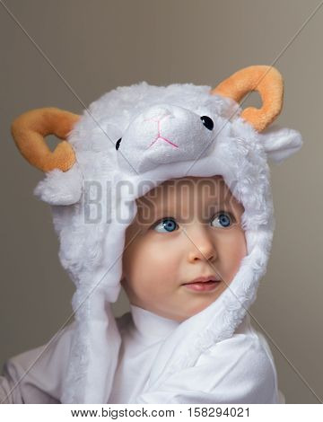 Closeup portrait of a cute adorable baby wearing a sheep hat hood with yellow horns and white shirt looking up on a light background New Year  concept studio
