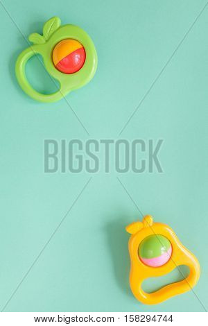 baby rattle on green background top view