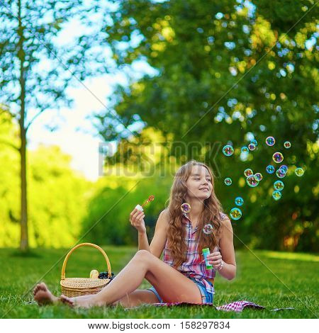 Girl Sitting On The Grass And Blowing Bubbles