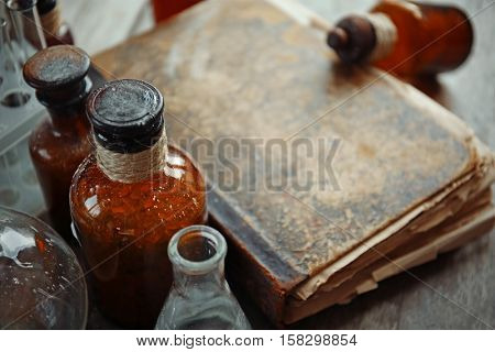 Old book with glass bottles, closeup