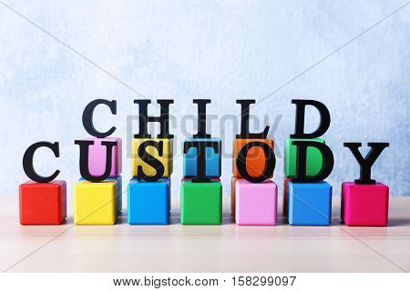 Words CHILD CUSTODY and multicoloured cubes on light background