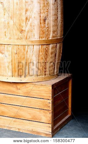 Light wooden cargo box and barrel on black background textured wallpaper copy space closeup
