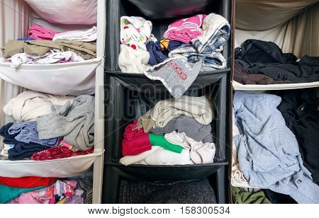 Messy untidy wardrobe closeup with colorful clothes for men women baby