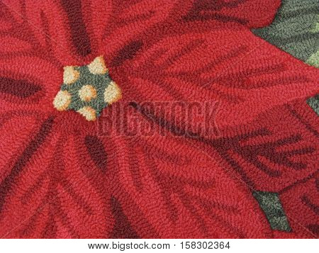 A hooked rug with poinsettia design adorns the floor at Christmas time.