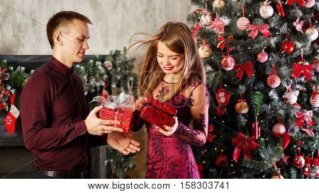 Loving couple and Christmas. Man and woman exchanging Christmas gifts. In the background a beautiful Christmas tree.