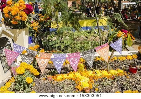 OAXACA, OAXACA, MEXICO - NOVEMBER 2, 2016: Grave decorated with flowers at the Oaxaca General Cemetery in Oaxaca City, Mexico.