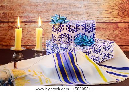 A table set for Shabbat with lighted candles challah bread and wine.