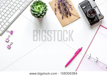 female white desktop with camera and flowers, keyboard, paper envelopes top view no one