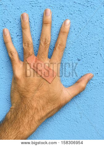 close up man hand on blue cement wall