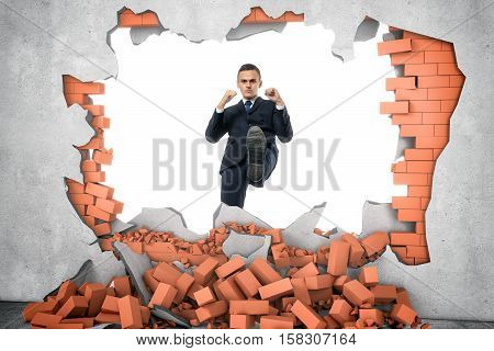Businessman ruins a brick wall with his leg isolated on the white background. Decisive actions. Brandnew business ideas. Destruction of impediments.