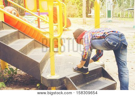 Child   tying shoes in the playground.Zoom in.0011