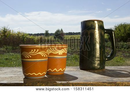 Stein and clay cups on the background of the rural landscape