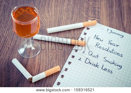 Vintage photo New years resolutions quit smoking and drink less written on sheet of paper and broken cigarette with glass of wine concept of healthy lifestyle