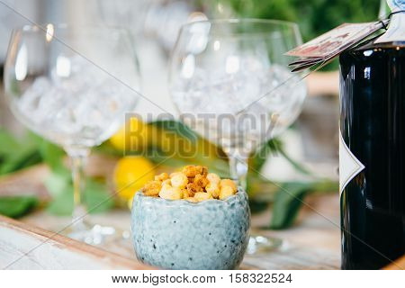 Close up composition of glasses with ice snack in bowl and gin tonic.