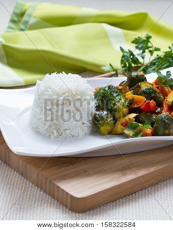 Rice and vegetables on white plate with with herbs and pepper on wooden bord