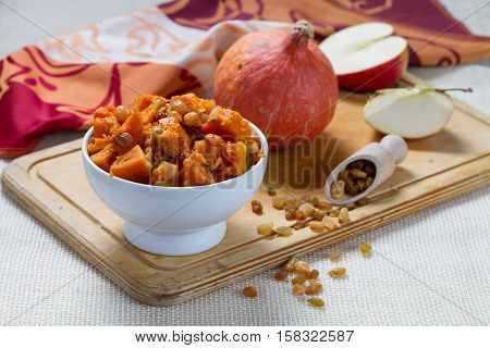 Pumpkin dessert with apple, cinnamon and raisins in white bowl on the wooden board