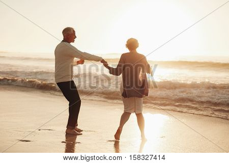 Senior Couple Having Fun At Beach