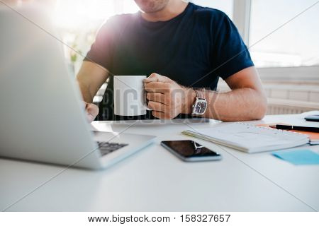 Cropped shot of young man with cup of coffee working on laptop. Business man working at his desk with coffee. Focus on hand.