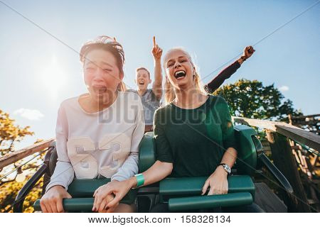 Enthusiastic Young Friends Riding Amusement Park Ride