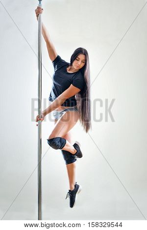 Young slim pole dance woman make exercise for pole