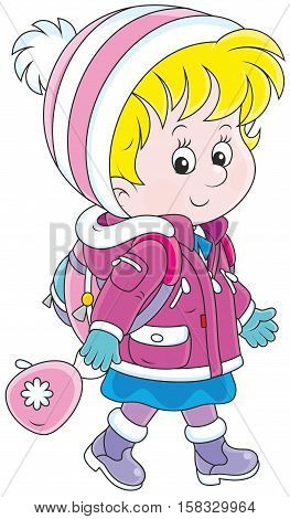 Little schoolgirl in a winter jacket and a warm hat and mittens going with a schoolbag